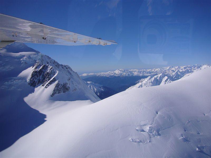 An aerial view of the glaciers, snow capped mountains and gorgeous glacial lakes.